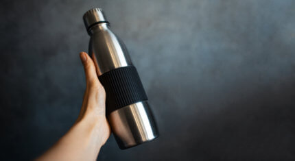 closeup of female hand holding steel thermo water bottle on the background of dark grey textured wall with copy space